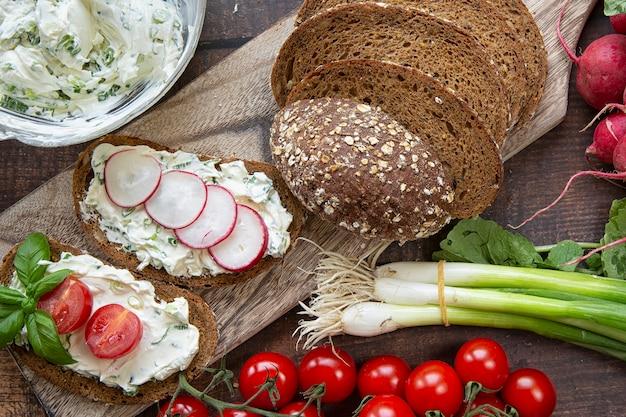 Preparação de sanduíches de verão queijo cottage com cebolinha, rabanetes e tomates. dieta ceto, estilo de vida saudável. fruta fresca.