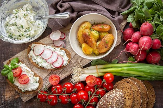 Preparação de sanduíches de verão queijo cottage com cebolinha, rabanetes e tomates. keto dieta, batatas fritas inteiras.