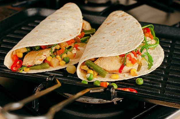 Preparação de tacos em uma panela de grelhar. fast-food mexicano tradicional.