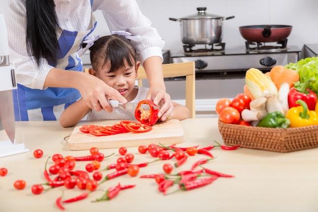 Preparação de um café da manhã familiar. a mãe asiática e a filha do bebê cozinham o café da manhã na manhã.