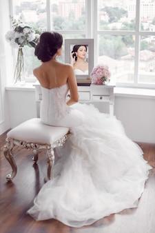 Preparação do casamento. bela jovem noiva vestido de noiva branco dentro de casa. modelo luxuoso à procura