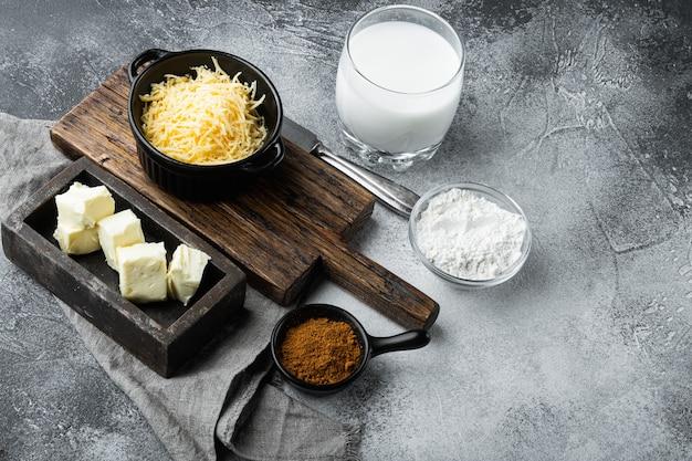 Preparação do conjunto de molho branco de queijo bechamel, na mesa de pedra cinza