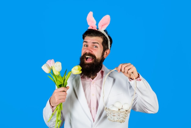 Preparação do dia de páscoa para a páscoa feliz barbudo homem com orelhas de coelho segurar a cesta com ovos homem com