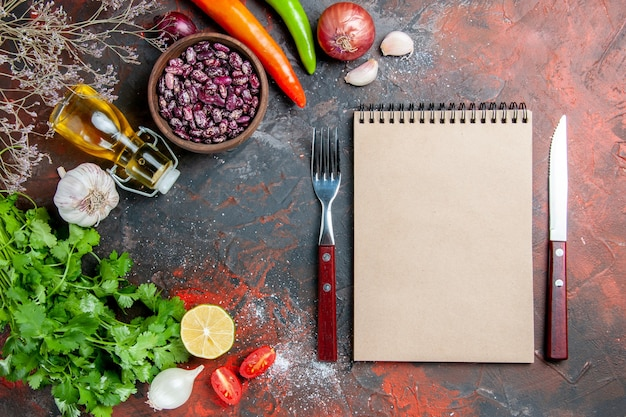 Preparação do jantar com alimentos e garrafa de óleo de feijão e um monte de tomate verde limão e caderno na mesa de cores misturadas