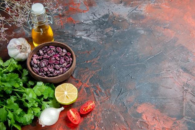 Preparação do jantar com alimentos e garrafa de óleo de feijão e um monte de tomate verde limão na mesa de cores misturadas