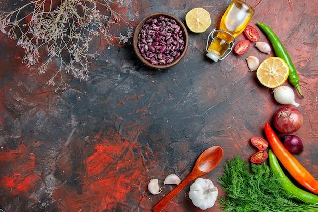 Preparação do jantar com garrafa de óleo, feijão, limão e um monte de verde na mesa de cores mistas