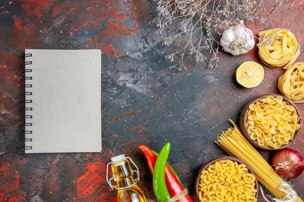 Preparação do jantar com massas cruas pimenta caiena amarradas umas nas outras com garrafa de óleo de corda, alho, limão e caderno na mesa de cores mistas