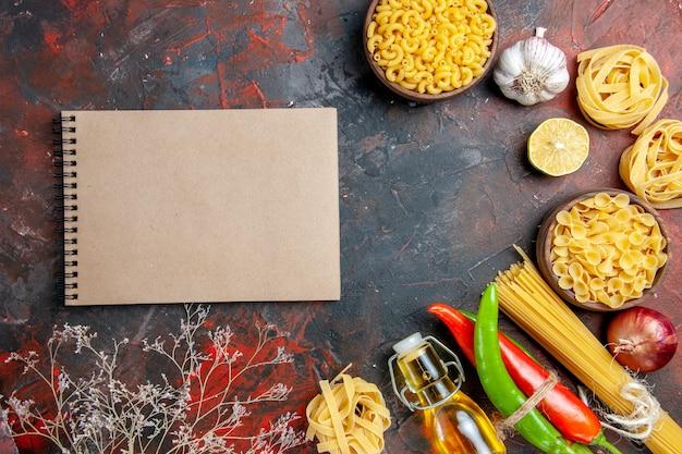 Preparação do jantar com massas crus, pimenta caiena amarradas umas nas outras com garrafa de óleo de corda, alho e limão e caderno com imagens de mesa de cores mistas