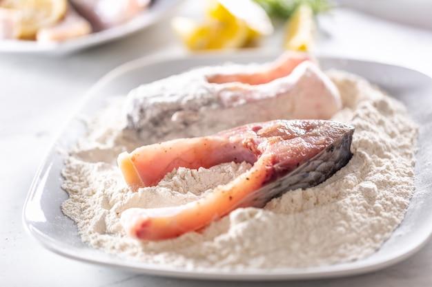 Preparação do peixe fresco antes da fritura envolvendo a farinha.
