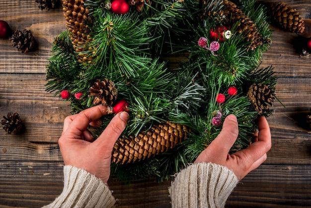 Preparação para as férias de natal. mulher que decora a grinalda verde do natal com pinhas e bagas vermelhas do inverno e bolas da árvore de natal