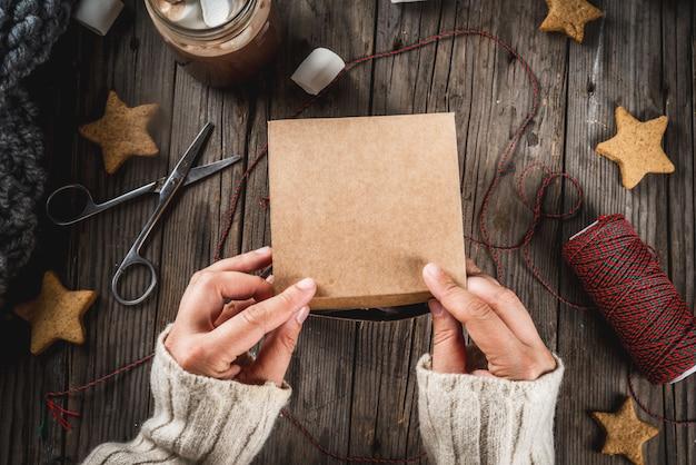 Preparação para as férias de outono e inverno. a pessoa embala os biscoitos como um presente em uma caixa de artesanato, fita de natal, mãos no quadro. mesa antiga rústica, espaço de cópia de vista superior