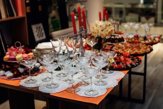Preparação para banquete ou festa copos de vinho, lanches e sobremesas. belo cenário de mesa festiva