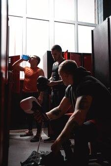 Preparação para boxeadores de grandes lutadores em roupas esportivas preparando luvas de boxe para treinamento em