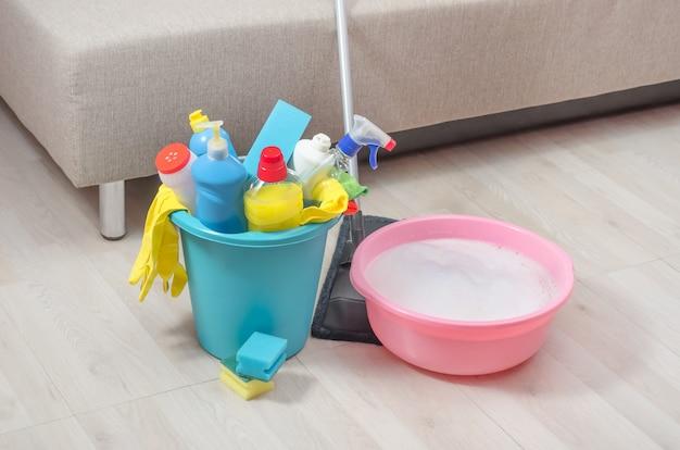 Preparação para limpeza na casa, no apartamento, balde com diversos agentes de limpeza e detergente diluído numa bacia no chão.