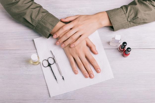 Preparação para manicure: mãos femininas, garrafas de laca e outras ferramentas na mesa