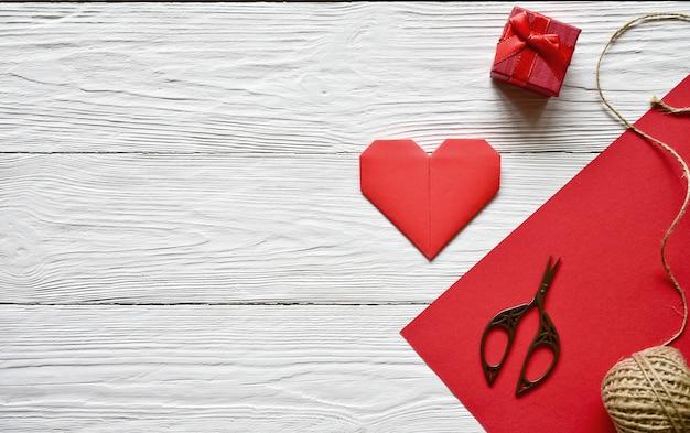 Preparação para o dia dos namorados. folha de papel vermelha, tesoura, coração de origami vermelho, novelo de barbante e caixa de presente em um artesanal de madeira branco. dia de são valentim