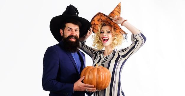Preparação para o halloween. casal feliz em chapéus de bruxas com abóbora. conceito de celebração e festa. 31 de outubro.
