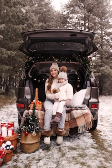 Preparação para o natal. mãe e filha se divertem brincando no porta-malas de um carro