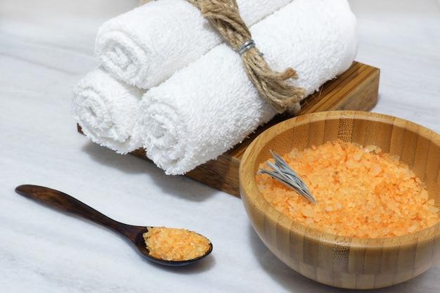 Preparação para o procedimento de spa - sal de banho laranja em uma tigela de madeira e colher e três toalhas brancas em uma caixa de madeira sobre uma mesa de mármore branco