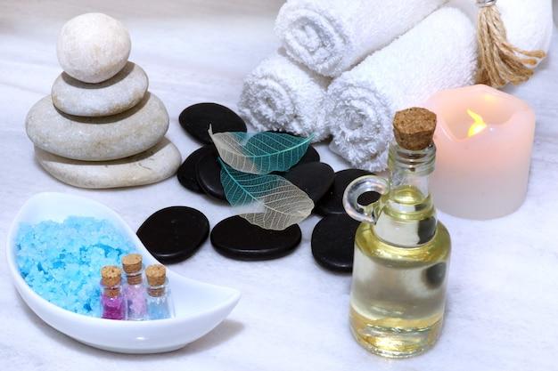 Preparação para o procedimento de spa, sobre uma mesa de mármore branco, óleo aromático, pedras e sal para massagem, toalhas macias em rolos e uma vela elétrica segura.