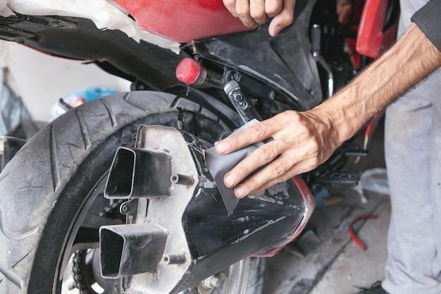 Preparação para pintar uma motocicleta. mão em uma lixa