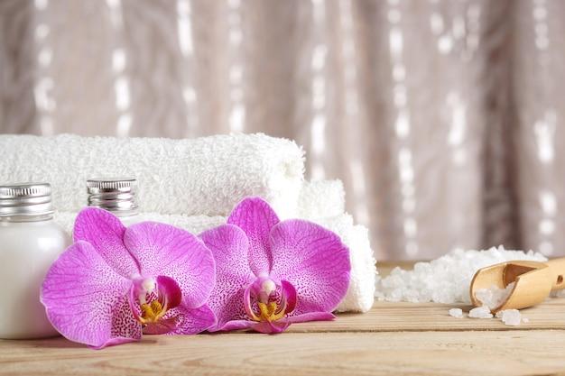 Preparação para procedimentos de spa, sal, toalhas, loção e flores brilhantes de orquídeas na mesa
