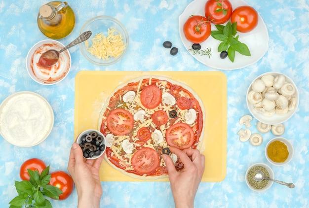 Preparação passo a passo de pizza vegetariana caseira, passo 8 - coloque azeitonas no queijo