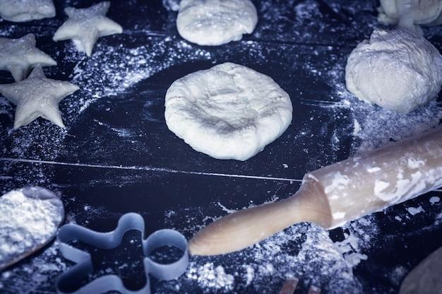 Preparações de massa para tortas caseiras e biscoitos em uma mesa de madeira escura. pastelaria caseira