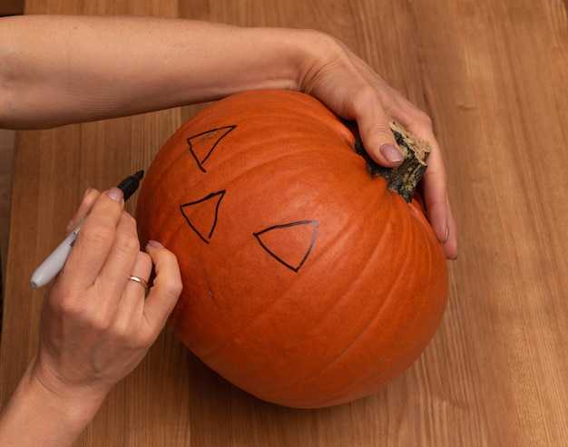 Preparações para o halloween, mãos de woomanns fazendo esboço na abóbora.