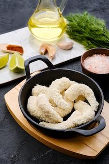 Preparado para fritar camarões crus em empanados de queijo com especiarias