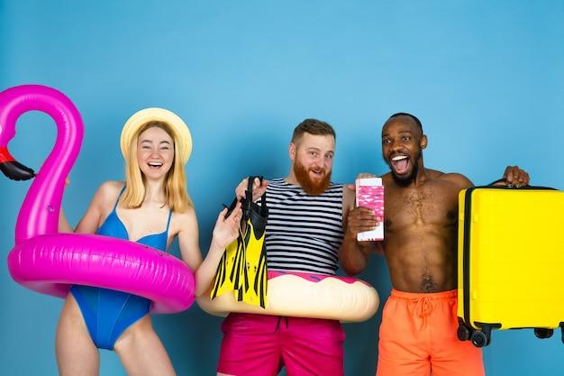 Preparado para viajar. jovens amigos felizes descansando e surpresos no fundo azul do estúdio. conceito de emoções humanas, expressão facial, férias de verão ou fim de semana. frio, verão, mar, oceano.