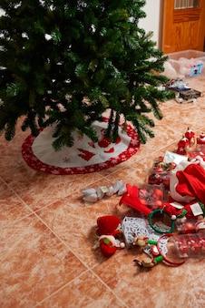 Preparando a árvore de natal em casa com decoração no chão