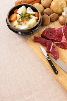Preparando a carne para a caçarola ou o guisado com ingredientes e faca na placa de desbastamento da cozinha.