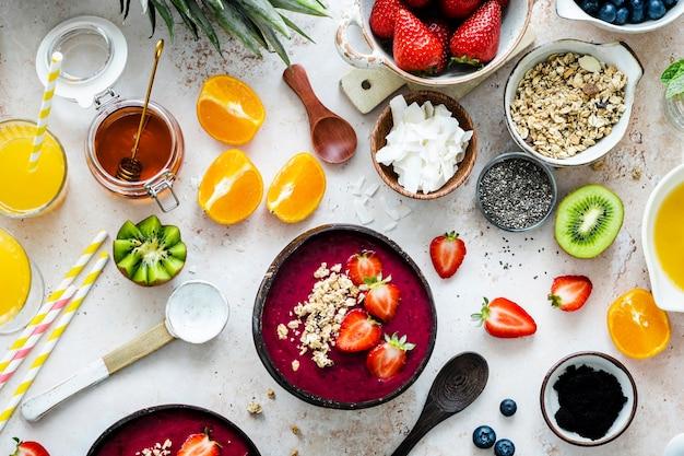 Preparando a tigela de açaí em estilo plano com frutas tropicais e grãos