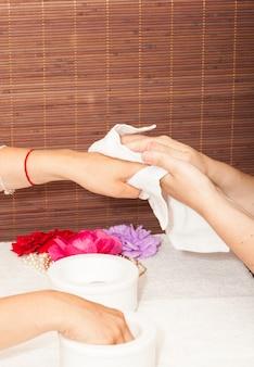 Preparando as mãos de uma mulher para uma manicure