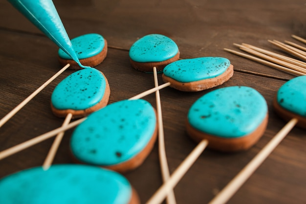 Preparando biscoitos de páscoa com glacê azul para decoração em mesa de madeira rústica closeup