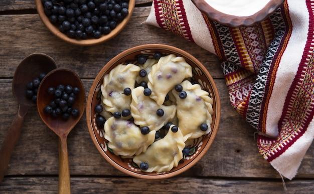 Preparando bolinhos com mirtilo. fazendo pierogi ou pyrohy, varenyky, vareniki. cozinha tradicional russa, o tradicional vareniki ucraniano feito à mão (bolinho de massa) com mirtilo por dentro