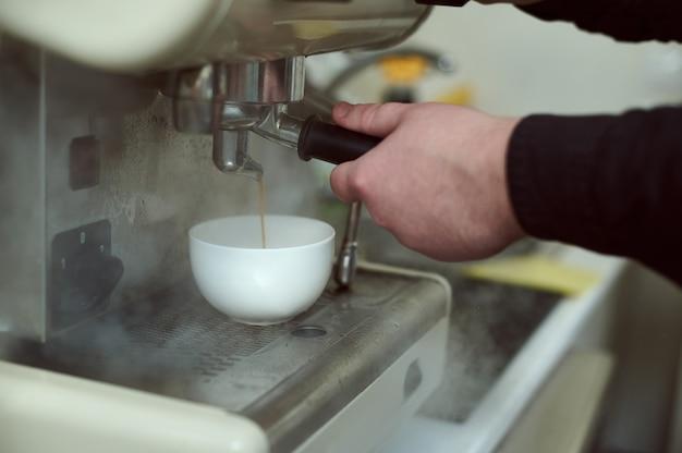 Preparando café expresso na cafeteira fumegante