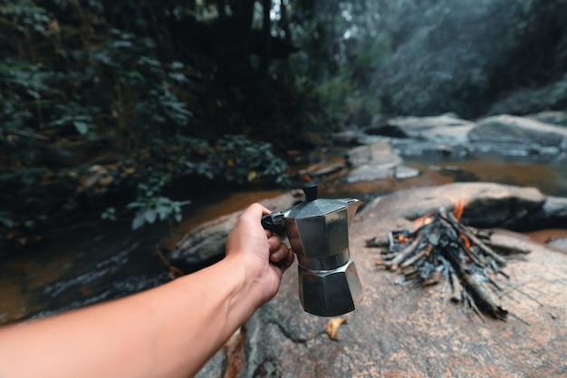 Preparando café na floresta com uma cafeteira moka