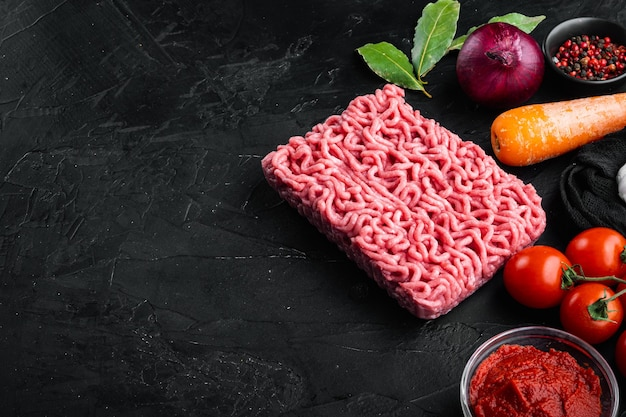 Preparando ingredientes de molho à bolonhesa, carne picada, tomate, conjunto de ervas, em uma mesa de pedra preta