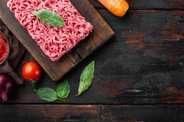 Preparando ingredientes de molho à bolonhesa, carne picada, tomate, conjunto de ervas, na tábua de madeira, na velha mesa de madeira escura, vista superior, camada plana