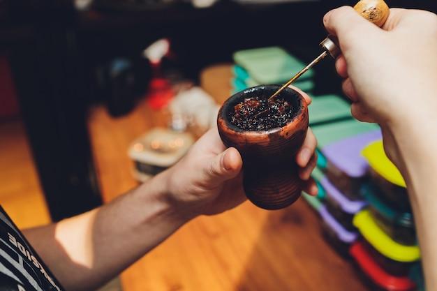 Preparando o narguilé para fumar, enchendo a tigela de barro com tabaco, mãos masculinas visíveis.