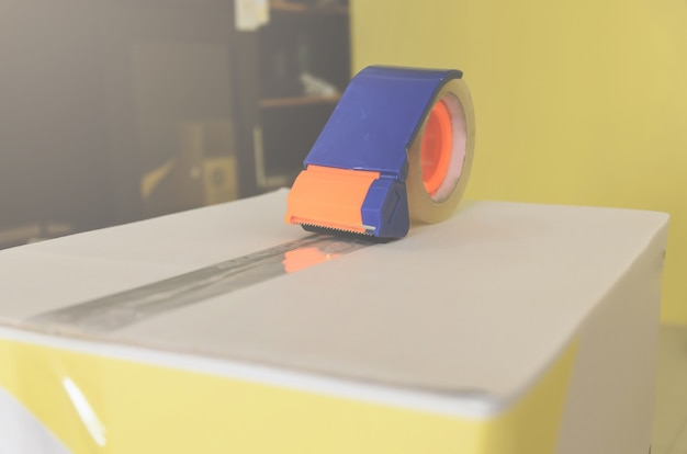 Preparando o pacote para o transporte com tesoura e cortador de fita adesiva.