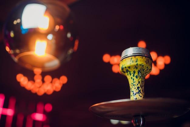 Preparando o shisha, também conhecido como narguilé ou narguilé, em um restaurante, colocando os carvões por cima. um costume do oriente médio.