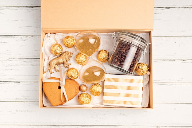 Preparando pacote de cuidado, caixa de presente sazonal com café, biscoitos e chocolates. cesta ecológica personalizada para a família e amigos para o natal em cores douradas.