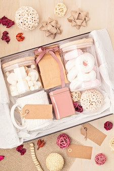 Preparando pacote de cuidados e caixa de presente sazonal com caixa de marshmallow, chá, café ou cacau e enfeite de natal