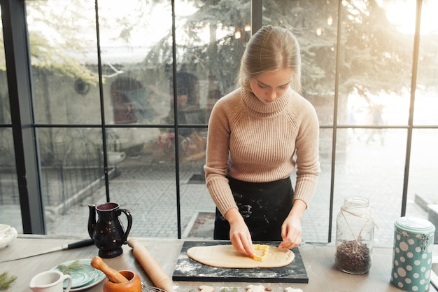 Preparando pão de gengibre com cortador de plástico