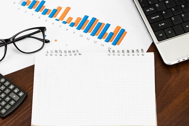 Preparando relatório. gráficos e tabelas azuis. relatórios de negócios e pilha de documentos na mesa de madeira