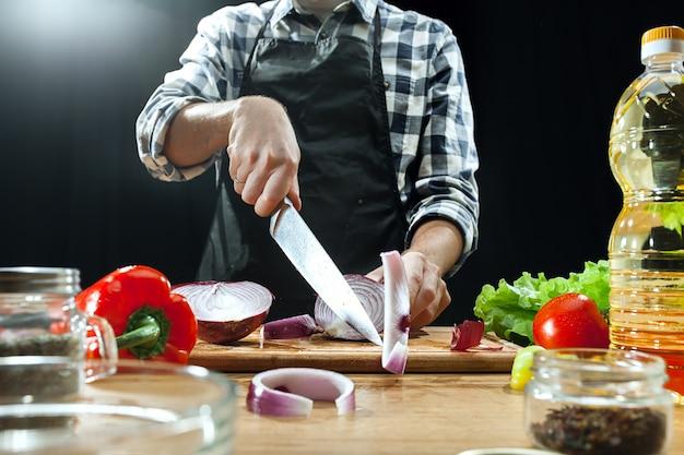 Preparando salada. chef feminino corte de legumes frescos. processo de cozimento. foco seletivo