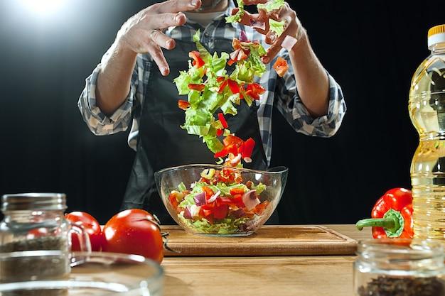 Preparando salada. chef feminino corte de legumes frescos.
